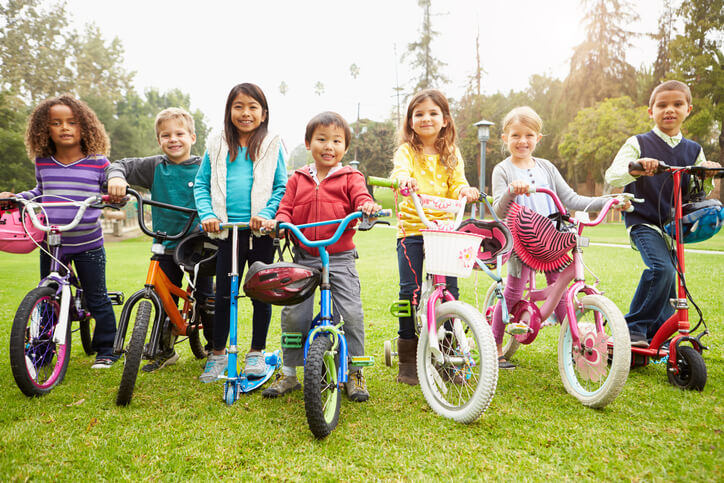 Young Children With Bikes And Scooters In Park Smiling To Camera