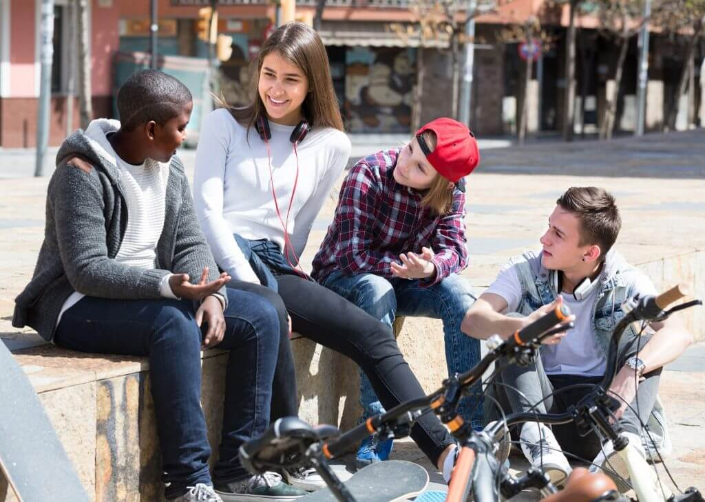 Group of european teens chatting near bikes  in sunny day